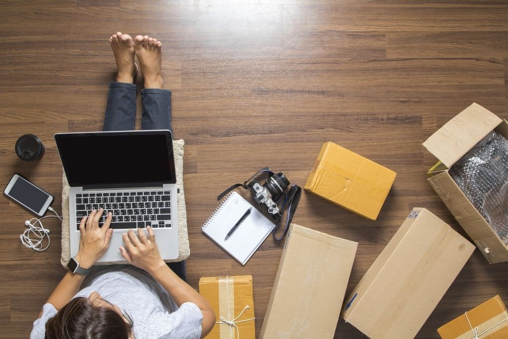 An eCommerce store owner on their laptop with packages next to her.