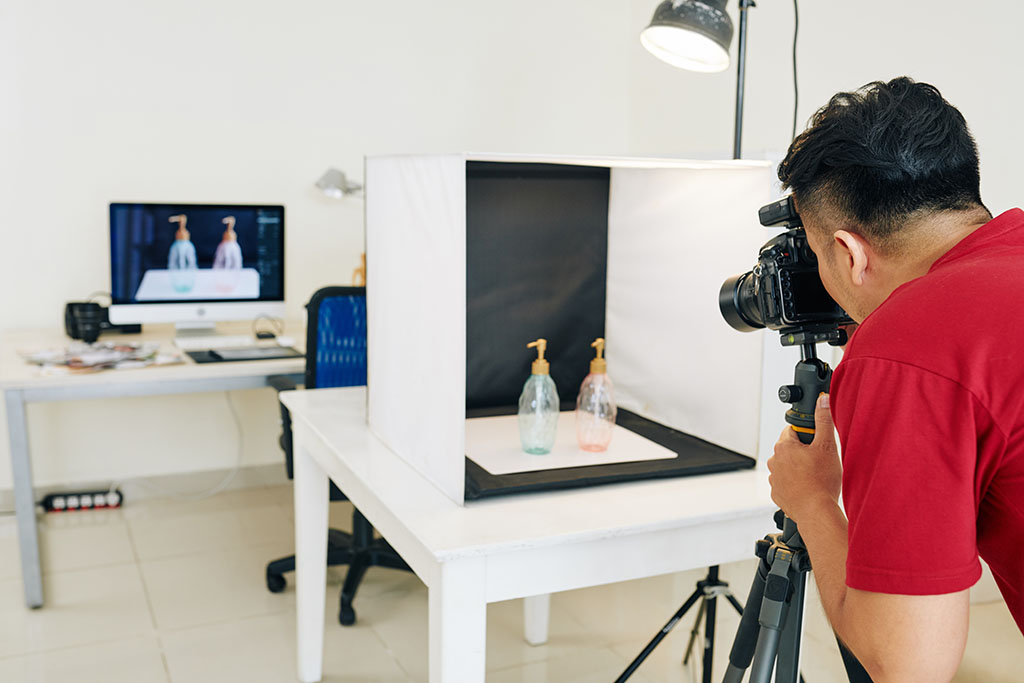 A young male amazon seller takes pictures of products in a photo lightbox.