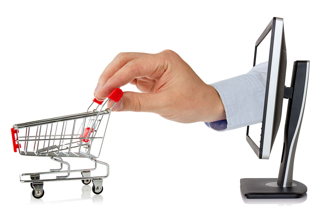 Hand pushes shopping trolley out of the laptop