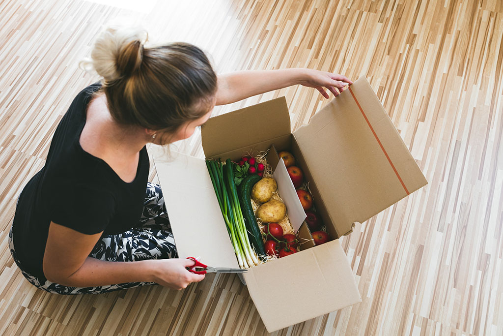 A woman opens a box of shipped groceries.