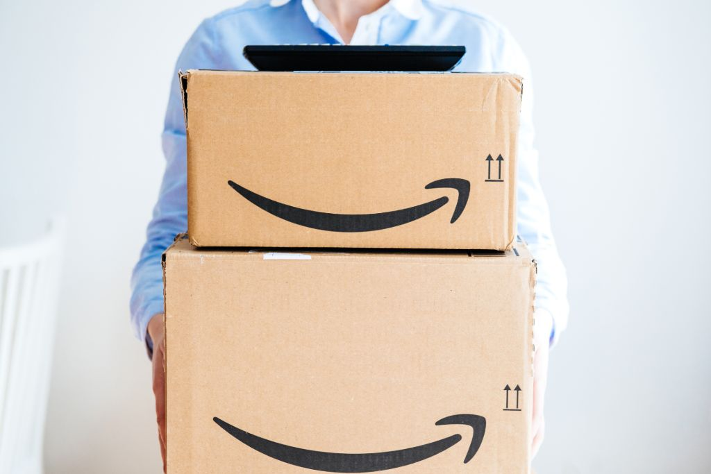 Person holds two large Amazon boxes